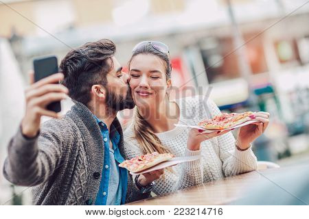 Couple eating pizza snack outdoors.They are sharing pizza and eating, make selfie photo