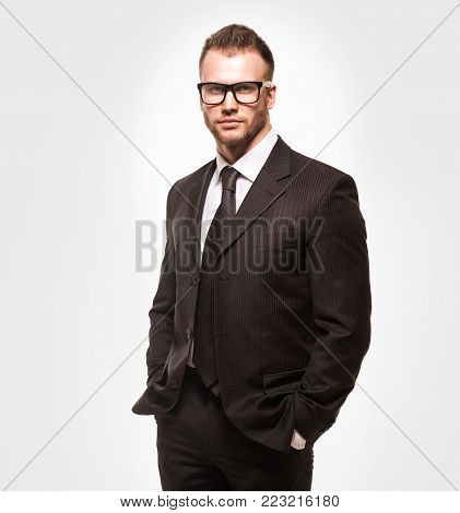 Young handsome businessmanman in black suit and glasses isolated on light grey studio background