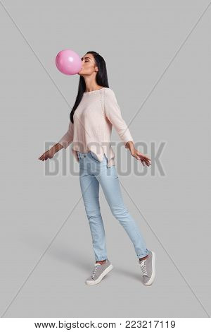 One more step and she will fly. Full length studio shot of attractive young woman in casual wear blowing up a pink balloon while standing against grey background