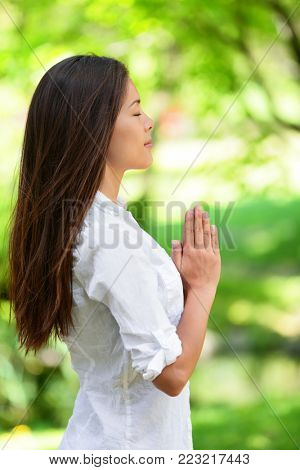 Young woman with hands clasped meditating in park. Side view of beautiful woman in casuals. Attractive female with eyes closed practicing yoga in nature.