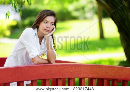 Young woman daydreaming at green summer park. Thoughtful female leaning with hand on chin. Attractive multiracial woman pensive sad and lonely thinking outside wondering about life.