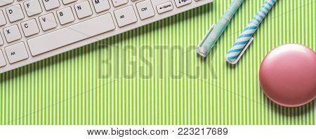 Green background with keyboard and girlish pens. Girl's blog concept