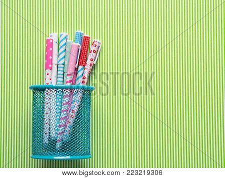 Colorful girlish pens on green striped background. Flat lay
