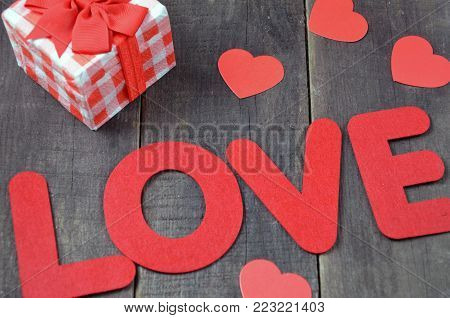 beautiful red heart ornaments on a wooden background on Valentine's Day, word love letters, inscription on Valentine's Day, feast of love in February