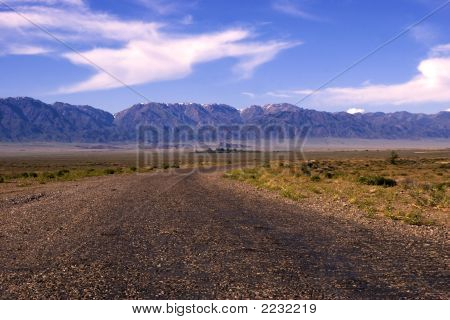 Perspective Road To Mountain At Desert In Sunrise