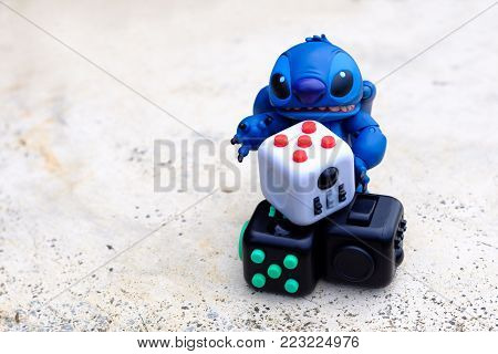 Songkhla, Thailand - July 3, 2017: Stitch playing Fidget Cube stress reliever, Fingers Toy (Relax)