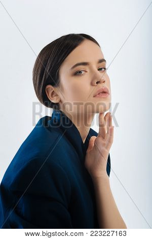 Beauty. Pretty unsmiling long-haired young woman staring and wearing a jacket and having a hairdo