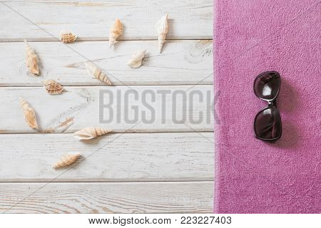 Beach towel and summer accessories on white wooden background. Travel concept. View from above. Blank mock up for advertising or packaging.