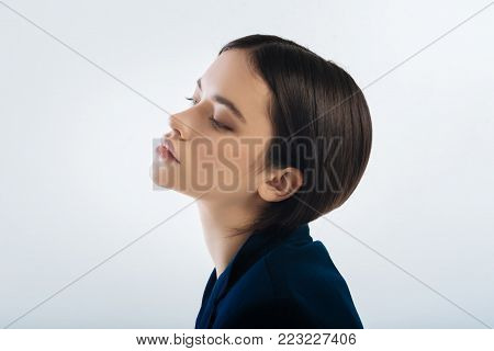 Reflective mood. Brunette musing earnest woman posing in profile while  closing eyes and  emerging in the thoughts