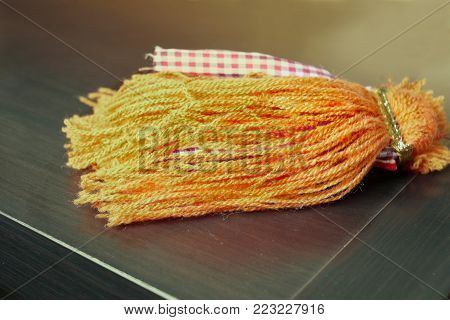 An orange curtain tassel laid on the wooden surface, filtered closeup