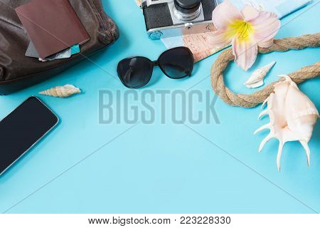 Travel set, sunglasses and summer accessories on blue background. View from above. Blank mock up for advertising or packaging.