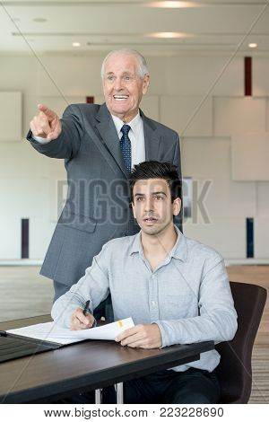 Amazed senior man showing unexpected results of business research to colleague. Shocked young male manager with documents listening to excited senior businessman. Astonishment concept