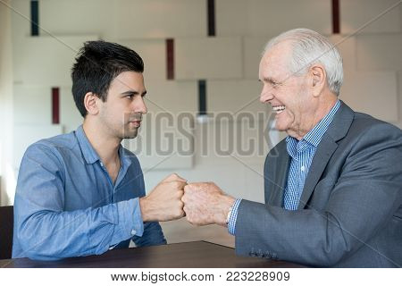 Cheerful colleagues bumping fists instead of handshake in office. Cheerful senior boss congratulating young employee with first results. Modern business mentor working with intern. Cooperation concept