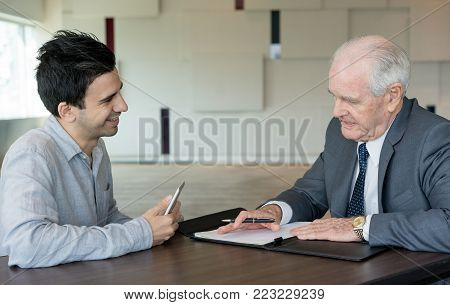 Concentrated businessman delving into contract while meeting with business partner. Cheerful young manager waiting for answer in office. Collaboration concept