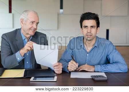 Confused male young accountant calculating budget using calculator at meeting. Misunderstanding man watching presentation while boss showing papers with another data. Preparing report concept