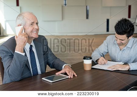 Deceitful senior businessman with cheesy grin talking to customer on phone and using tablet. Emotional male manager leading communication while his colleague filling document. Sale occupation concept