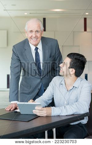 Happy senior businessman working with financial advisor while planning budget. Cheerful ambitious male executive analyzing report with colleague in office. Technology concept