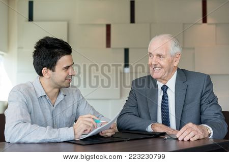 Cheerful businessmen discussing agreement and making adjustments in office. Positive insurance agent filling application form with senior businessman. Management concept