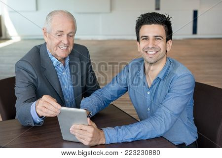 Happy managers working on new project. Cheerful ambitious handsome financial advisor showing report on tablet to businessman. Analytics concept