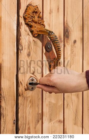 Female Hand Shut Or Open Wooden Door With Key Close Up.