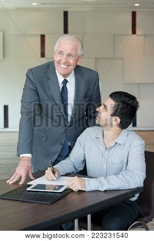 Positive senior executive enjoying results of business analysis while watching presentation with colleague in office. Excited businessman making notes in report at meeting. New achievement concept