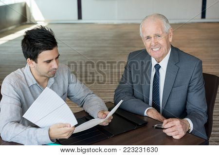 Positive gray-haired senior businessman at meeting with lawyer. Happy successful managing director satisfied work of assistant or advisor. Signing contract concept