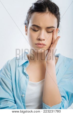 Horrible headache. Stressful pleasant adorable woman closing her eyes while standing in blue shirt and putting arm on her face