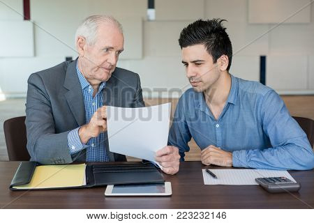 Serious senior boss showing clause in contract and explaining it to young colleague. Displeased confident businessman working with accountant while they discussing report in office. Paperwork concept