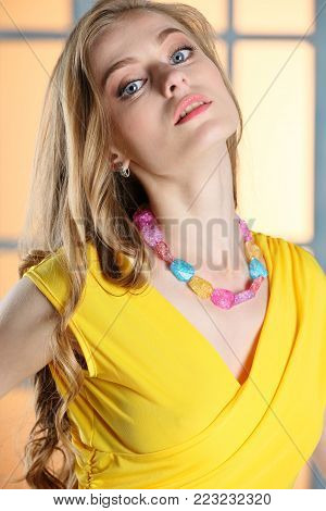 Close-up portrait of a slender young pretty woman with blond long hair and beautiful face with large expressive eyes. Gorgeous cute adult fashion girl model posing.