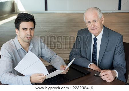 Serious successful businessmen signing agreement in board room. Confident boss and his male assistant viewing documents discussing aspects. Modern enterprise concept