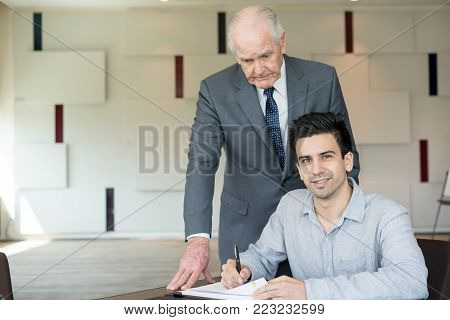 Smiling businessman signing agreement with successful company. Happy entrepreneur collaborating with business organization. Or senior businessman supporting young startupper. Administration concept