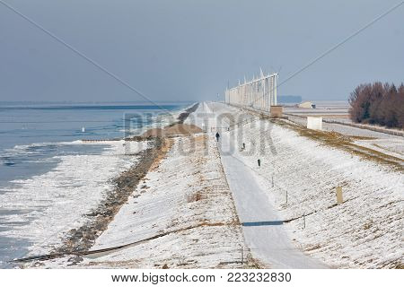 Dutch winter landscape with frozen sea and drifting ice near Urk. At background row of windturbines along the dike