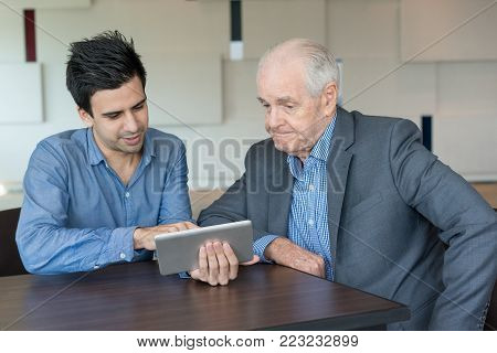 Upset senior businessman listening to colleagues report while watching online presentation on tablet. Serious male executive being skeptical about new strategy. Agenda concept