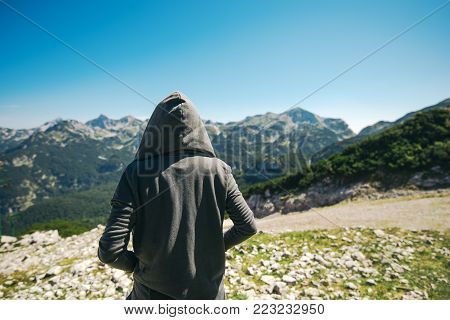 Mountain hiker at high viewpoint looking at the valley. Female tourist person in hooded jacket at mountain top enjoying the view.