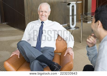 Smiling senior man in white shirt and tie sitting in leather armchair and holding interview. CEO conversing with job candidate. Business meeting and employment concept