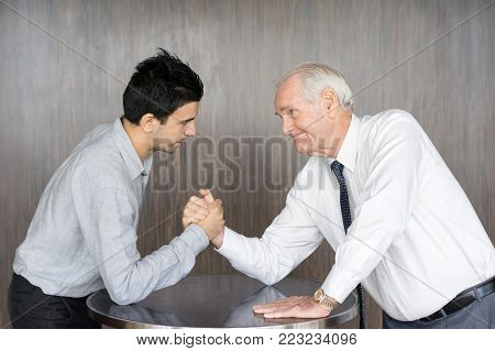 Senior man in white shirt and tie and young business partner competing in arm wrestling. Metaphor for two business competitors. Business meeting and competition concept