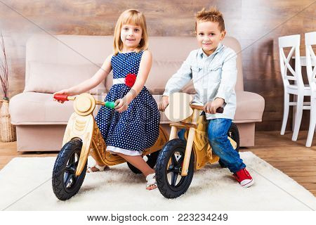 Happy smiling little children riding a wooden runbikes at home in the living room