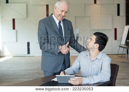 Smiling senior man in suit showing  thumb up gesture to junior colleague. Boss encouraging hardworking manager. Business and corporate hierarchy concept