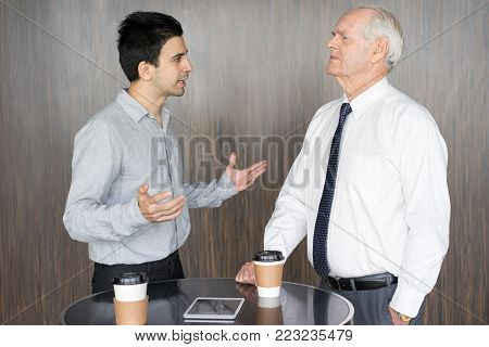 Dissatisfied senior man in tie having quarrel with young businessman. Two business competitors arguing during coffee break. Business meeting and negotiation concept