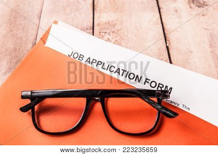 You are hired - concept. The glasses lie on an envelope with a job search form.