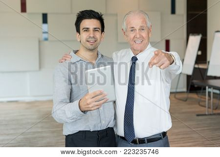 Content senior man in tie pointing at camera and slapping young colleague on shoulder. Mentor and young employee with tablet advertising e-learning course. Business meeting and coaching concept