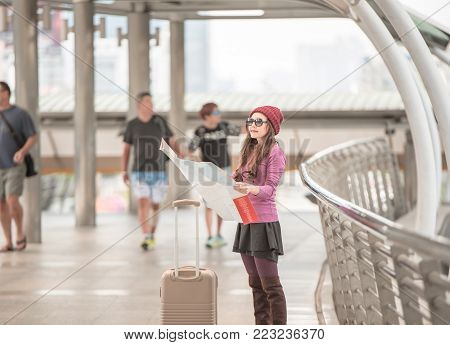 Woman traveler looking at travel map in airport walkway with travel bag or luggage.Concept of woman travel