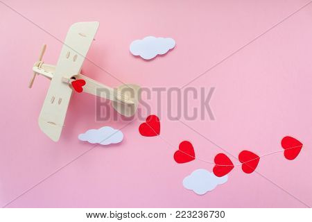 Happy Valentines Day. Wooden Children's Plane On A Pink Background With Red Heart, And Garland In Th