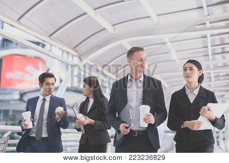 Happy Business colleagues walking outside office & talking to each other. Businessman talk and hold coffee cup