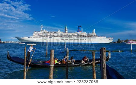 VENICE, ITALY - JUNE 19: Giant cruise ship inside Venetian Lagoon against a little traditional gondola. A very big issue for the preservation of Venice fragile enviroment and city historic heritage June 19, 2016 in Venice, Italy