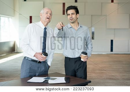 Manager pointing at screen and discussing presented new project with CEO.  Young employee showing something out of window to boss. Business and presentation concept