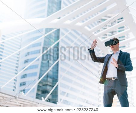 Concept Simulation Business, Smart businessman in a suit wear vr goggles with city town background.