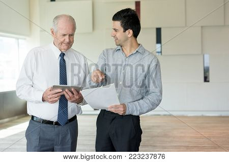 Senior businessman checking his calculation with cost sheet of young partner. Senior executive with tablet calculating cost of new solution for company. Business meeting and deal concept
