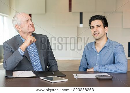 Serious senior man in suit and junior businessman at conference room. Two business people thinking over and discussing collaboration. Business meeting and negotiation concept
