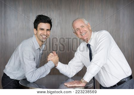 Smiling senior man in tie and young business partner competing in arm wrestling for fun. Office workers having fun during break. Business meeting and work balance concept